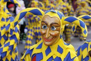 blau-gelb gekleideter Narr mit Narrenkappe