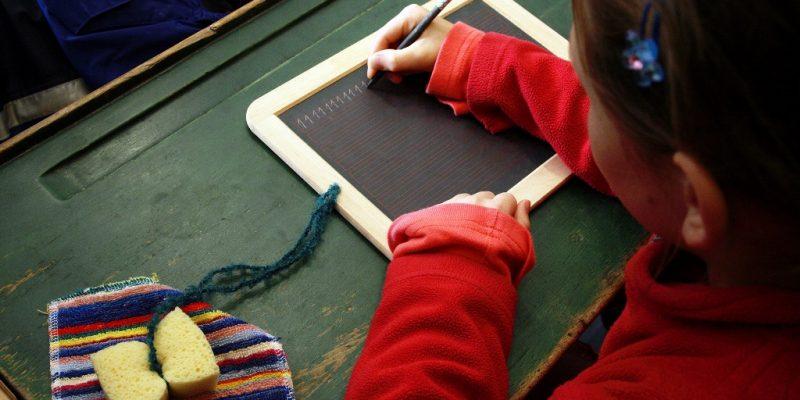 Kind schreibt auf einer Schiefertafel in der historischen Schulstube des Freilichtmuseums Massing