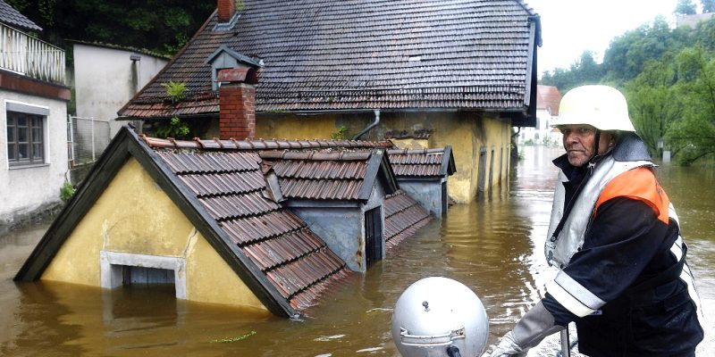 """Feuerwehrmann vor dem überschwemmten Gasthaus """"Zur Fels'n"""""""