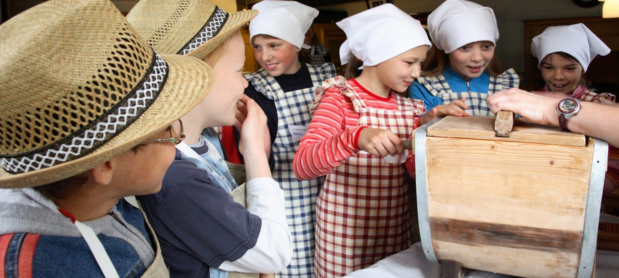 Kinder beim Butterrühren im Freilichtmuseum