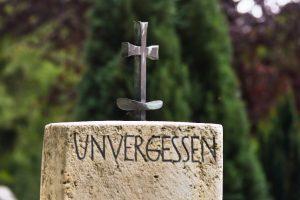 """Grabstein mit Kreuz und Inschrift """"Unvergessen"""""""