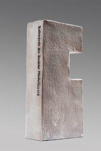 Ein graufarbener Ziegelstein als Kulturpreis