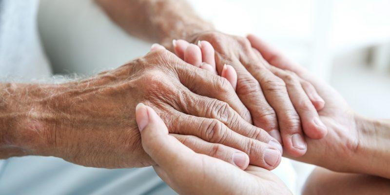 Pflegekraft hält Hände eines alten Menschen