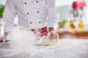 Bäcker rollt Teig mit der Hand